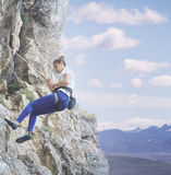 Woman rock climber on the cliff Stock Photography