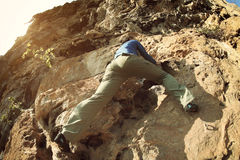 Woman rock climber climbing at seaside mountain cliff Stock Photo