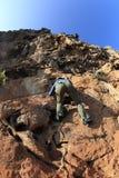 Woman rock climber climbing at seaside mountain cliff Stock Photography