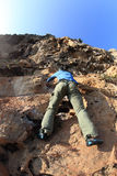 Woman rock climber climbing at seaside mountain cliff Stock Images