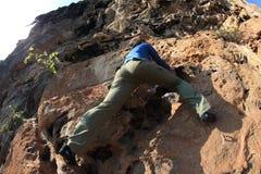 Woman rock climber climbing at seaside mountain cliff Stock Image