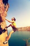 Woman rock climber climbing at seaside mountain rock wall Royalty Free Stock Image