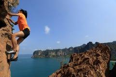 Woman rock climber climbing at seaside mountain rock Stock Photography