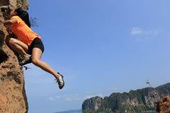 Woman rock climber climbing at seaside mountain rock Royalty Free Stock Image