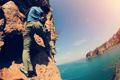 Woman rock climber climbing at seaside mountain rock Stock Image