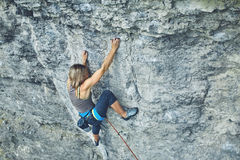 Woman rock climber climbs on the cliff Stock Images