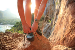 Woman rock climber tying shoelace on rock Stock Photos