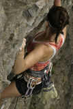Woman rock climbing. Overhead view of young woman rock climbing on mountain Royalty Free Stock Photo