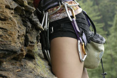 Woman rock climbing. Details of woman rock climbing with equipment on belt Royalty Free Stock Images