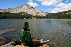Woman on rock by lake Stock Photo