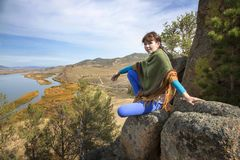 Woman on a rock in the mountains Stock Photo