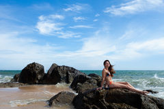 Woman on the rock in ocean Stock Photography