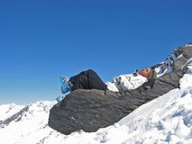 Woman on a rock with skiwears. Woman in mountain with skiwears on a rock in the medium of snow Stock Photos