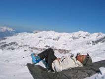 Woman on a rock with skiwears. Woman in mountain with skiwears on a rock in the medium of snow Stock Photography