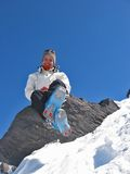 Woman on a rock with skiwears. Woman in mountain with skiwears on a rock in the medium of snow Royalty Free Stock Photos