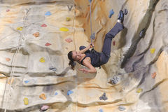 Woman on rock wall in sport centre Royalty Free Stock Images