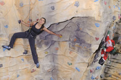 Woman on rock wall in sport centre Stock Photography