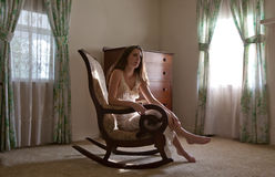 Woman in Rocking Chair in Beautiful Room. A gorgeous image of a beautiful young woman sitting in an old fashioned rocking chair in a farmhouse room with large Stock Images
