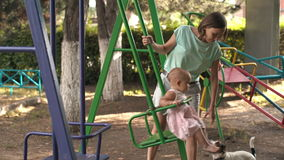Woman rocking my daughter on the swing. Woman rocking her infant daughter on a swing on a Sunny summer day stock video footage
