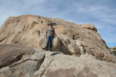 Woman on Rocks in Joshua Tree National Park. Horizontal landscape with a middle aged Caucasian woman standing on rocks at Joshua Tree National Park in California stock images