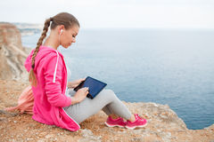 Woman on a rocky beach with a tablet in the spring Stock Photos