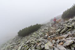 Woman rocky mountain slope fog. Royalty Free Stock Photography