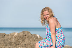 Woman on a rocky sea shore. Young long blond hair woman wearing blue dress sitting on rocks at a sea shore and smiling Stock Photo