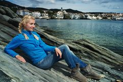 Woman on a rocky seashore. Blond woman against Cadaqués city view Stock Photography