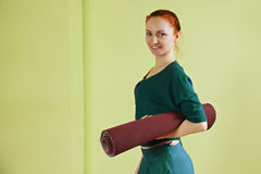 Woman with rolled mat Royalty Free Stock Photos