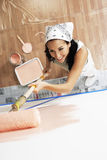 Woman With Roller Applying Pink Paint On A Wall Royalty Free Stock Photos