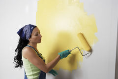 Woman With Roller Applying Yellow Paint On A Wall Stock Photography