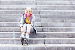 Woman with roller blades sitting on stairs Stock Photography