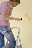 Woman With Roller On Ladder Royalty Free Stock Image
