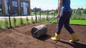 Woman with roller leveling soil earth in her apartment house yard. Gimbal motion stock footage