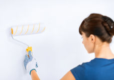 Woman with roller and paint colouring the wall Royalty Free Stock Image