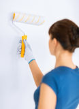Woman with roller and paint colouring the wall Stock Photos