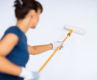 Woman with roller and paint colouring the wall Royalty Free Stock Photo
