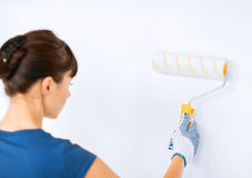 Woman with roller and paint colouring the wall Stock Photo