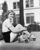 Woman in roller skates sitting on a sidewalk Stock Image