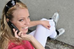 Woman ON rollerblades calling with mobilephone. Young smiling woman wearing rollerblades calling with mobilephone outdoors Stock Photography