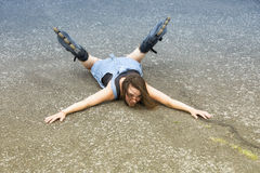 Woman with rollerblades lying on asphalt after accident Royalty Free Stock Photography