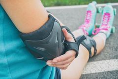 Woman rollerskater putting on elbow protector pads on her hand royalty free stock photo