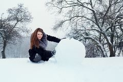 A woman is rolling a big snow ball Stock Images