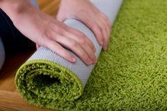 Woman rolling carpet Stock Photos