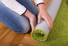 Woman rolling carpet Stock Images