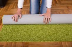 Woman rolling carpet Royalty Free Stock Photos