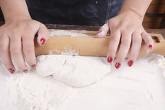 Woman rolling dough with rolling pin. Royalty Free Stock Image