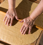 Woman rolling dough on a table Stock Images