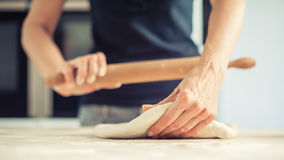 Woman rolling dough on wooden table with wooden rolling pin. Close up Stock Photo