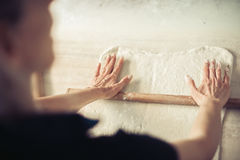 Woman rolling dough on wooden table with wooden rolling pin. Close up Royalty Free Stock Photography